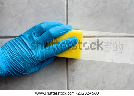 Cleaning sponge held in hand while cleaning bathroom with chinese lettering (cleaning in english translation) - stock photo