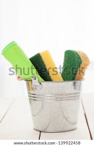 Cleaning sponges in a silver pail on a white wooden table - stock photo
