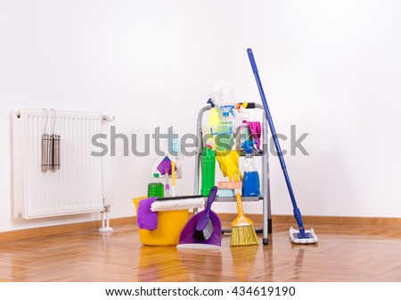 Cleaning supplies and equipment on ladder on parquet in the corner of the room - stock photo