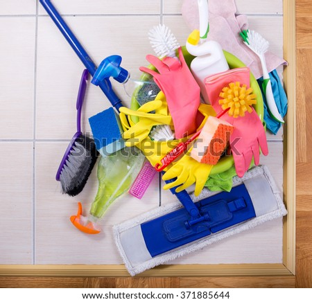 Cleaning supplies on a pile on tiled floor. Large group of colorful cleaning tools. Top view