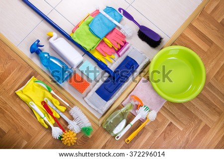 Cleaning supplies on tiled floor and parquet. Large group of colorful cleaning tools. Top view - stock photo