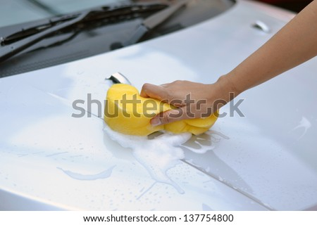 Cleaning the car with a sponge and soap suds on a bonnet - stock photo