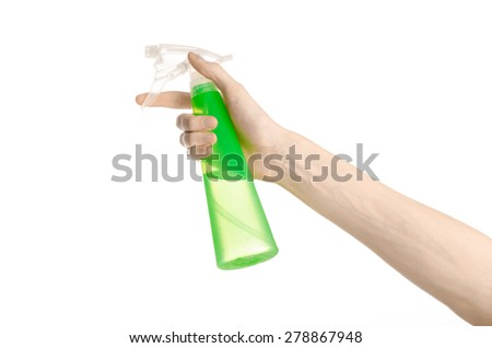 Cleaning the house and cleaner theme: man's hand holding a green spray bottle for cleaning isolated on a white background in studio - stock photo