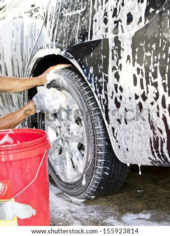Cleaning the wheel on a car with a sponge - stock photo