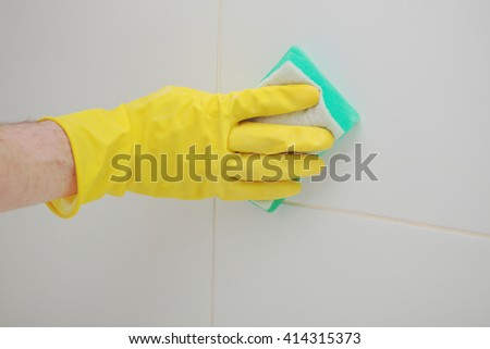 Cleaning tiled wall in a bathroom using cleaning sponge