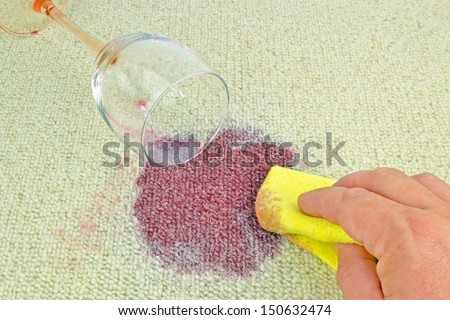 Cleaning up a spilled glass of red wine on a carpet - stock photo