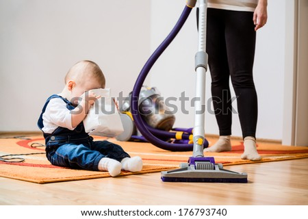 Cleaning up the room - woman with vacuum cleaner, baby looking to biscuits packet - stock photo