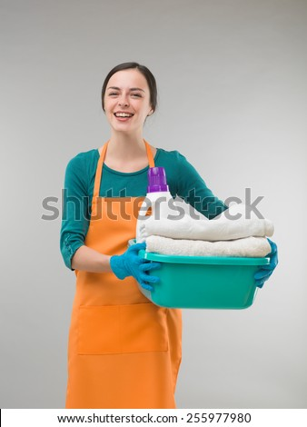 cleaning woman having fun while holding clean towels - stock photo