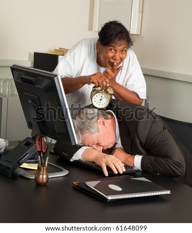 Cleaning woman holding an alarm clock next to a sleeping office worker