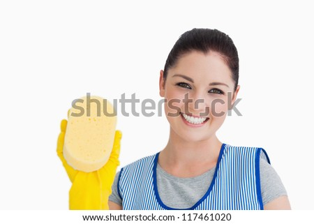 Cleaning woman showing a sponge on white background - stock photo
