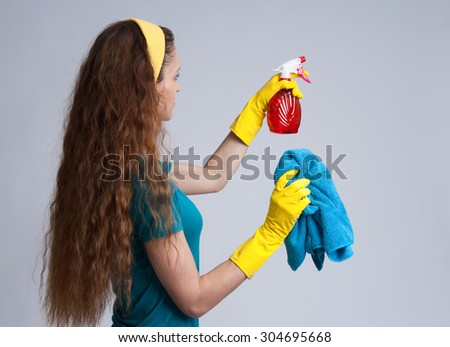 cleaning woman wearing yellow rubber protective gloves holding red spray. Cleaning service concept - stock photo