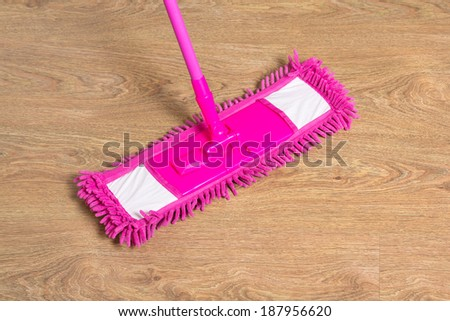 cleaning wooden floor with wet pink mop - stock photo
