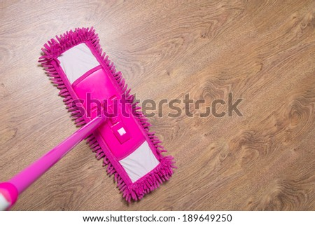 cleaning wooden parquet floor with wet pink mop - stock photo