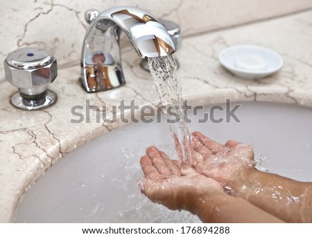 Cleanliness is the guarantee of health. Baby hands under running water - stock photo