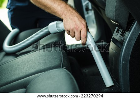 Cleanning a car by using vacuum cleanner - stock photo