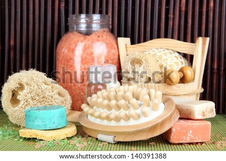 Cleanser, brush and cosmetics for shower on table on bamboo background