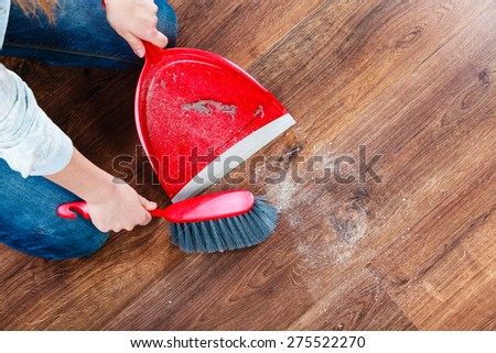 Cleanup housework concept. Closeup cleaning woman sweeping wooden floor with red small whisk broom and dustpan indoor - stock photo