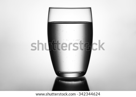 Clear and full glass of water black and white - stock photo