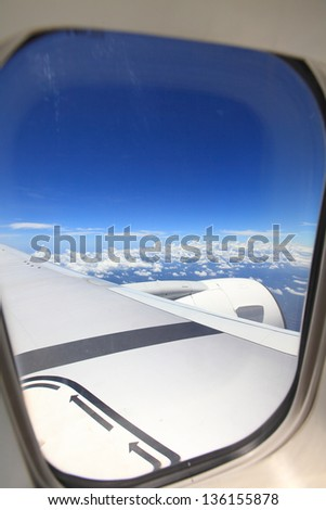 Clear and sky as seen through window of an aircraft - stock photo