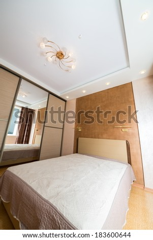 Clear bedroom with closet, large mirror and chandelier. - stock photo