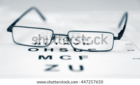 Clear Black modern glasses on a eye sight test chart. - stock photo