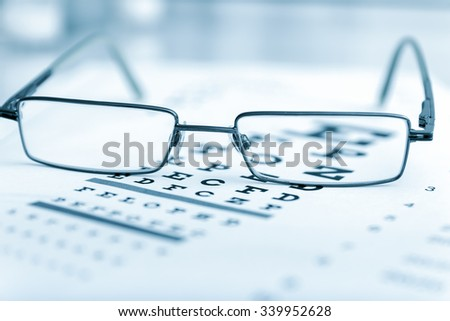 Clear Black modern glasses on a eye sight test chart..toned image - stock photo