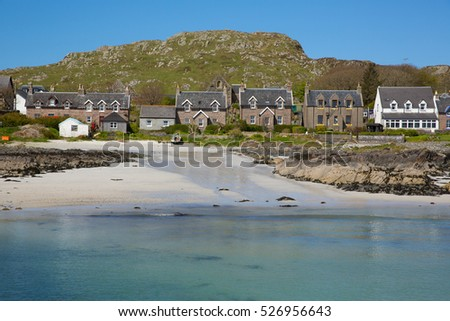 Clear blue sea and houses Scottish island of Iona Scotland uk Inner Hebrides off the Isle of Mull west coast of Scotland a popular tourist destination known for the abbey