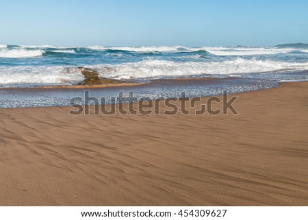 Clear blue skies and sea at low tide with waves breaking over a small rock and patterns on the beach sand on a South African coast