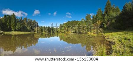 Clear blue sky and calm lake waters reflecting the pretty greenery of the Cotswold countryside. Stitched panoramic image detailed when viewed large. - stock photo