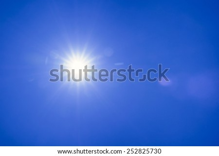 Clear blue sky sun light with Real Lens flare out of focus - stock photo