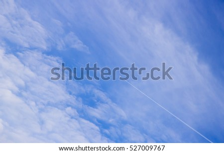 Clear blue sky with a few fluffy clouds