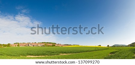 Clear blue summer sky over gently rolling patchwork farmland with pretty wooded boundaries, in the beautiful surroundings of the Cotswolds, England, UK. - stock photo
