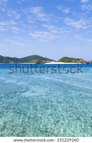 Clear blue tropical water of a coral lagoon and deserted islands on the horizon, Zamami Island of the Kerama Islands National Park, Okinawa, Japan - stock photo