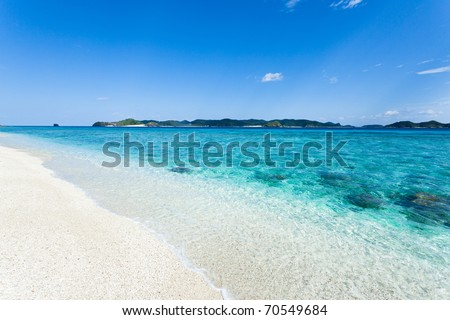 Clear blue water wave lapping white sand tropical beach on the deserted island in the coral lagoon, Kerama islands, Okinawa, Japan - stock photo