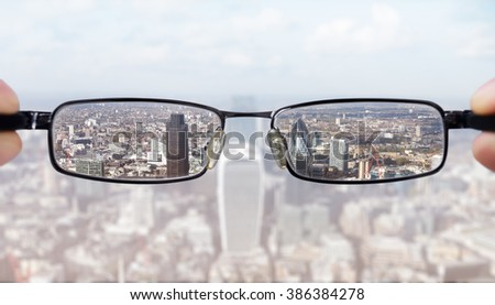Clear business vision concept businessman looking at the financial district of the city of London - stock photo