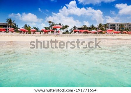 Clear calm waters lap the white sands of an umbrella studded Grace Bay Beach, Turks and Caicos - stock photo