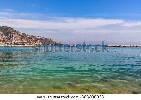 Clear coastal water of Mediterranean sea and small yacht on background of mountain in Menton - small town on French Riviera.