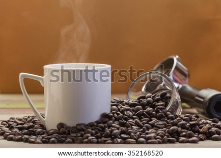 Clear coffee cup with beans on grunge brown background - stock photo