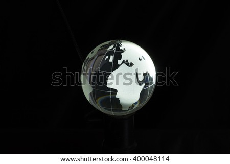 Clear crystal globe, isolated on black background. - stock photo