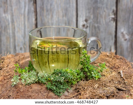 Clear cup containing an infusion or herbal tea made from Thyme a healing plant used as a cure for digestion,  flatulence and abdominal pain and it is antiseptic.