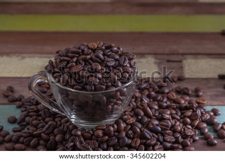 Clear cup with coffee beans - stock photo