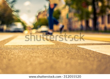 Clear day in the big city, pedestrian crossing the road. View from the pedestrian crossing, image in the yellow-blue toning - stock photo