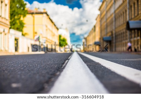 Clear day in the big city, the lights of the approaching car. View of the road at the level of the dividing line - stock photo
