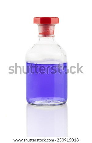 Clear glass bottle with purple liquid and red stopper. - stock photo
