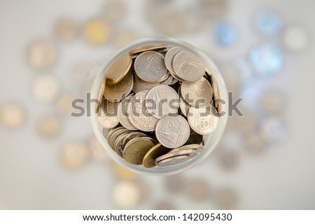 Clear glass jar for tips with money isolated on white. Thailand coins - stock photo