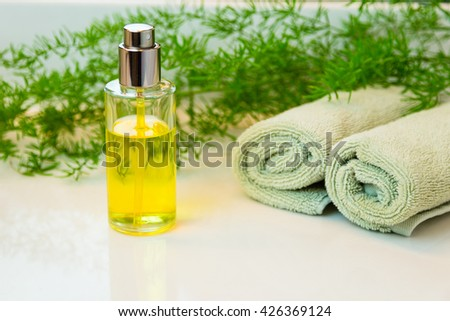 Clear glass spray bottle with yellow liquid. Rolled green towels in a spa setting. Green plant decor in background. Bathroom white countertop.