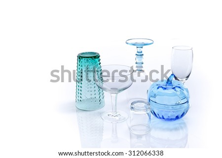 Clear glasses of variety shapes and colors on white background