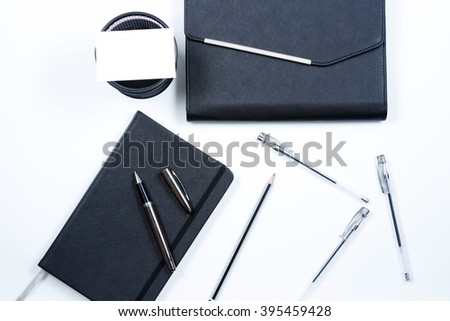 Clear Note Book with clear name card, group of pen arrange in flatlay with white background. Selective focus with shallow depth of field. - stock photo