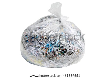 clear plastic trash bag filled with confetti shredded documents containing sensitive information such as medical bills, credit card and bank statements, and other personal info - stock photo