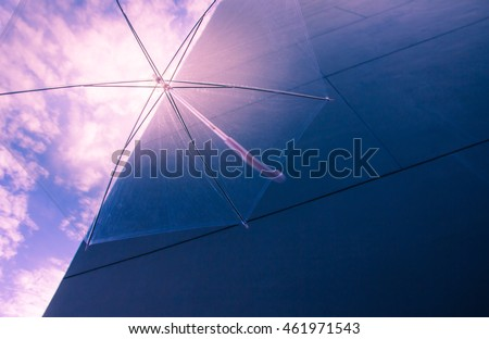 Clear plastic umbrella flying sunshine on a blue sky and wall background